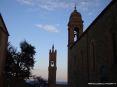 Montalcino (SI) - Sulla destra il campanile della chiesa di S.Agostino, sullo sfondo la torre del palazzo comunale al tramonto in una fredda serata di febbraio